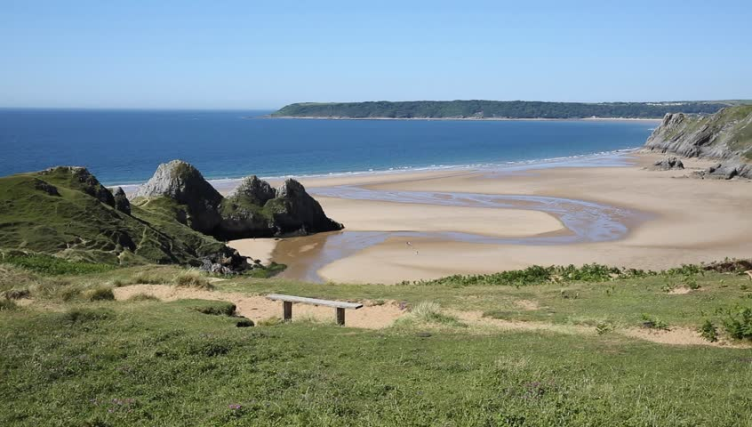 View of Three Cliffs Bay the Gower Peninsula Swansea Wales uk from the east with a wooden bench seat