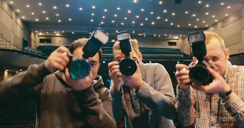 Three crazy photographers trying to make the best shot. Paparazzi flahes blinking one after another