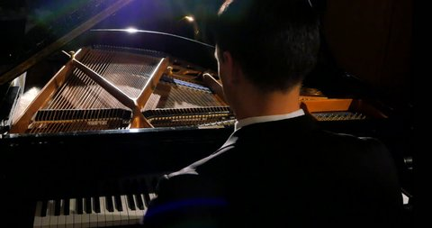 4K Tracking Shot of Male Pianist Playing Beautifully on Stage with Grand Piano