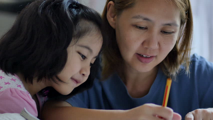 Little Asian girl with mother doing homework in the bed room