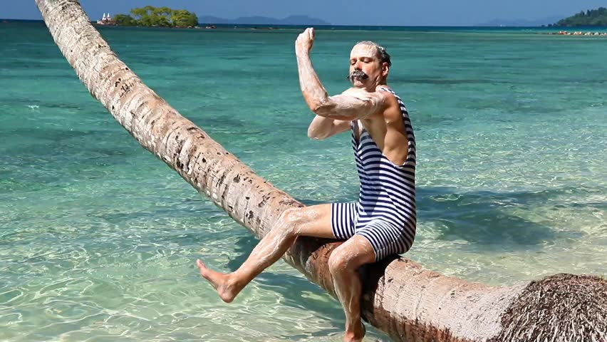 Man in retro swimsuit sitting on a palm tree above the sea and soap his body