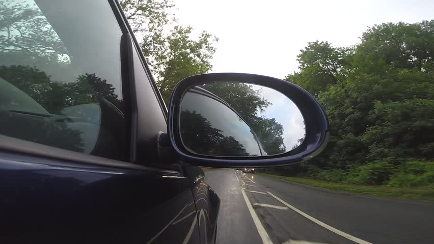 POV of wing mirror of blue diesel car driving through forest in Wiltshire, UK