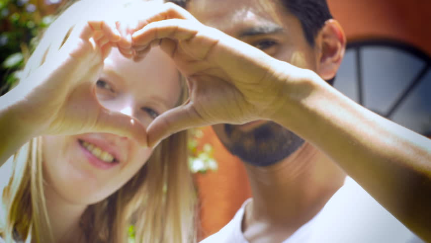 An attractive multi-racial 20's couple smiles at the camera and makes a heart with their hands with heads together and a hand held shot.