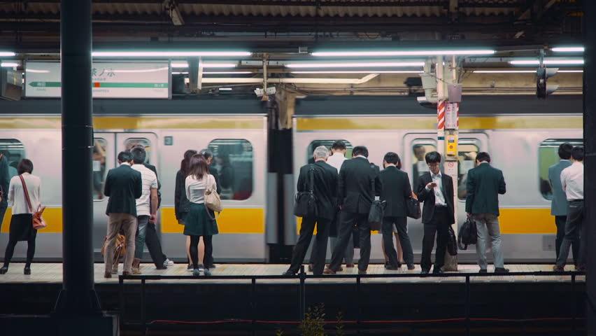 TOKYO - JUNE 1 2015: People wait  to board trains at the subway station in Ochanomizu, Tokyo, Japan.