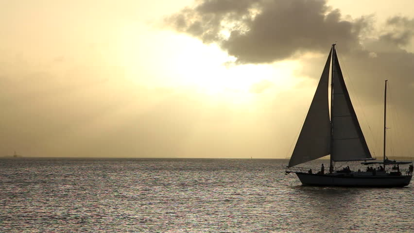 Silhouetted sailboat moves across the water in front of the setting sun in Key West, Florida.