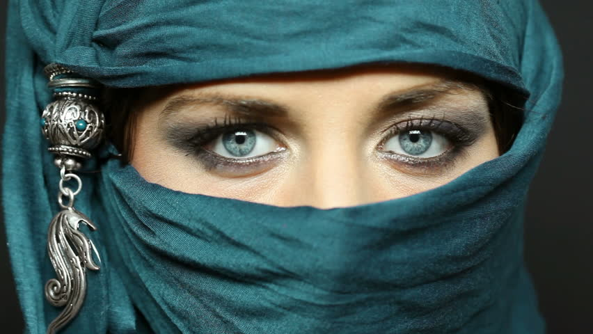 Portrait of an arabic young woman with her beautiful blue eyes in traditional islamic cloth niqab. Close up of a beautiful muslim woman looking at camera.