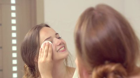 Beauty smiling teenage girl cleaning her face with a cotton pad and cleansing lotion. Young happy woman enjoying her skin smiling at the mirror, Skincare concept. Slow motion 240 fps. HD 1080p