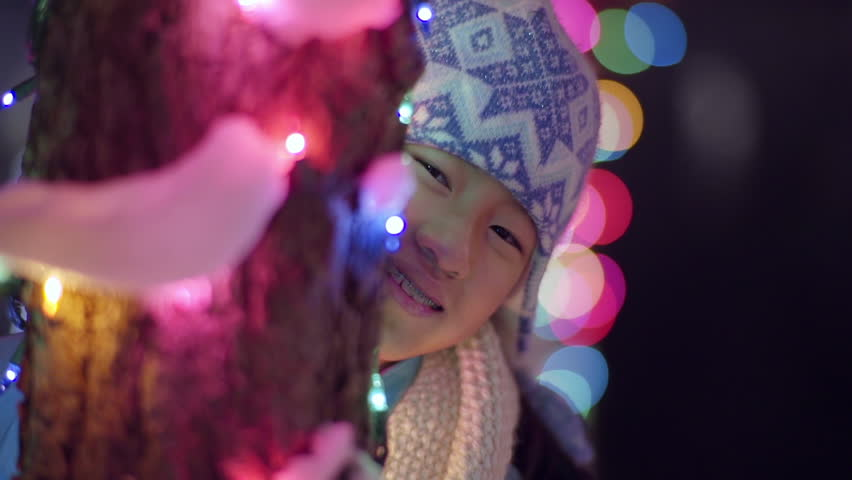 Playful Little Asian Girl Hides Behind Snow Covered Tree Lit For The Holidays, She Peaks Out And Smiles (Slow Motion) | Shutterstock HD Video #11026175