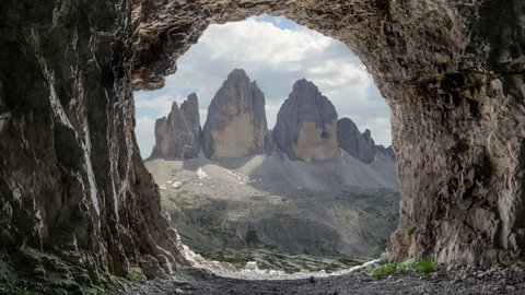tre cime di lavaredo peaks as seen from inside a cave where soldiers use to sleep during the second or first world war