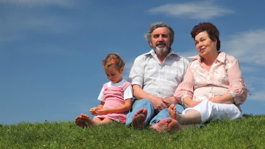 happy grandparents and grandchildren holding hands run down grass