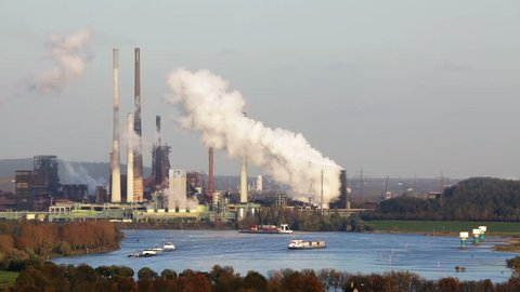 A large steaming coking plant in the distance with some ships on Rhine River in the foreground. Shot in Moers with view to Duisburg, Germany.