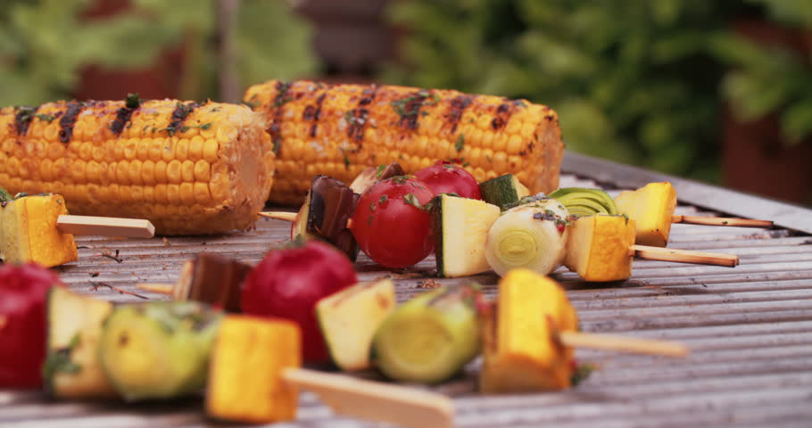 Fresh corn, vegetable kebabs, vine tomatoes and asparagus grilling on an outdoor barbecue