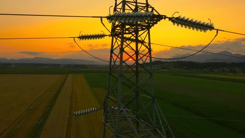 AERIAL: Flying up the high voltage electricity tower and power lines at sunset above the beautiful agricultural field