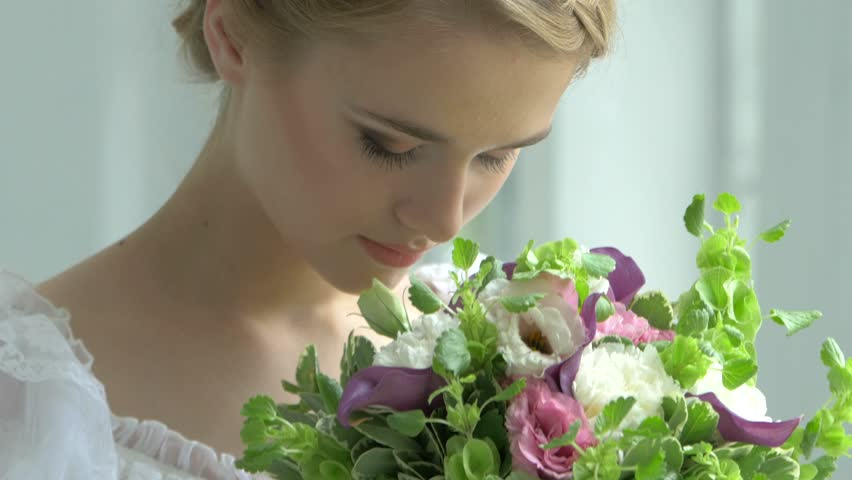 Beautifaul blonde girl in vintage white dress with charming bouquet of flowers, smelling, watching at the camera  #11112305