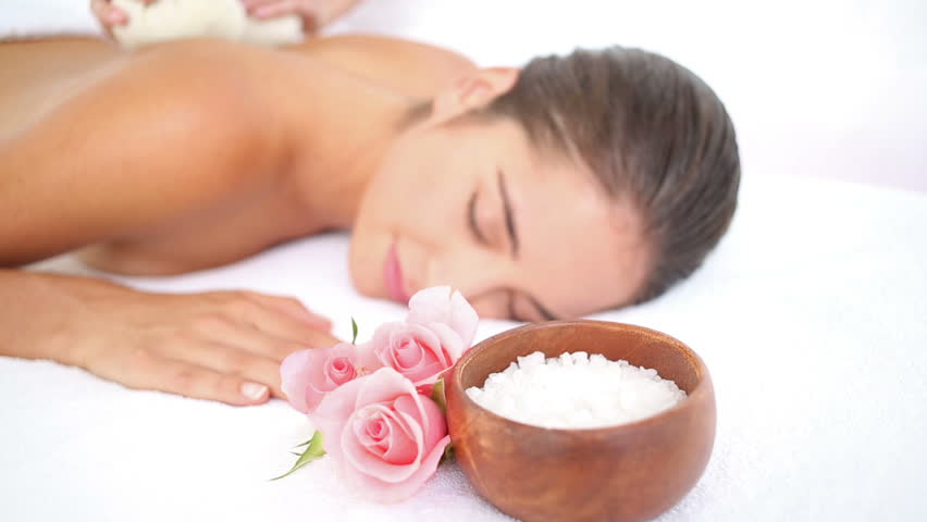 Woman enjoying a herbal compress massage at the health spa in slow motion
