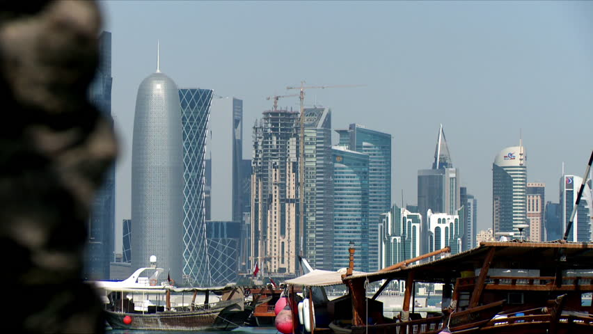 A close up tilt shot of high rise buildings in Doha, Qatar with traditional boats docked in front, with date trees either side of the shot | Shutterstock HD Video #11143745
