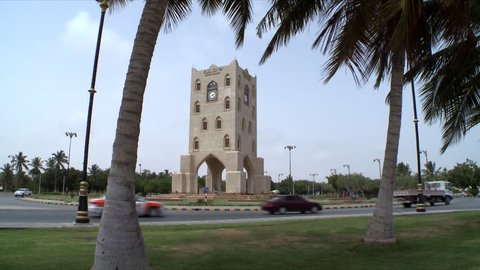 A static shot showing the Burj A'Nahdah on a roundabout in Salalah, Oman as cars circle round and date trees frame the shot