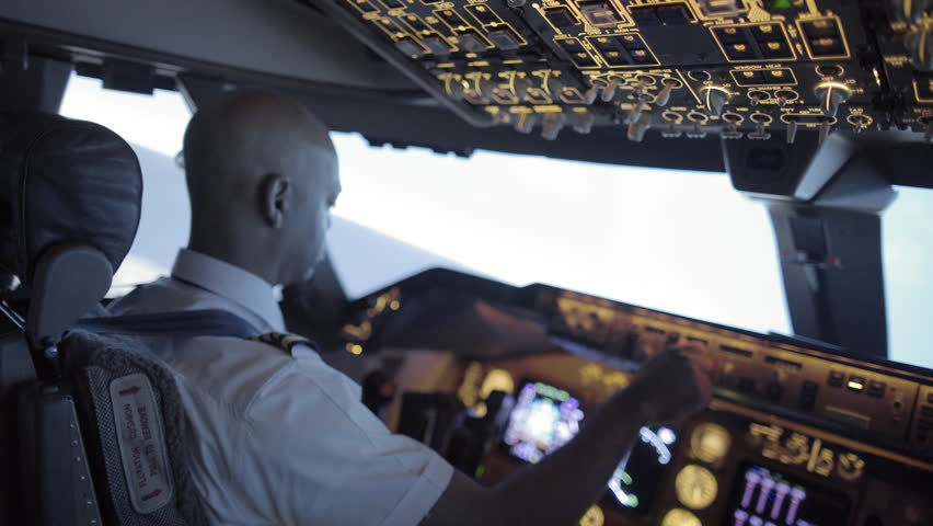 Rear angle view over pilot's shoulder as he adjusts instruments and flies a jumbo jet.  Hand-held camera with strong angle and racking focus, originally recorded in 4K.