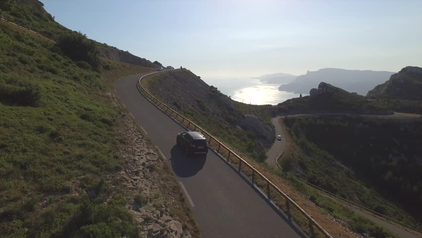 AERIAL: Car driving up the mountain pass above the ocean at beautiful summer sunset