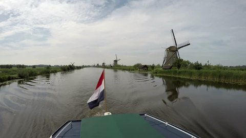 Dutch flag on the back of a boat on a canal in Kinderdijk Childrens Dike windmills Unesco World Heritage Unique Dutch sight and the most popular tourist attraction in Holland The Netherlands 4k