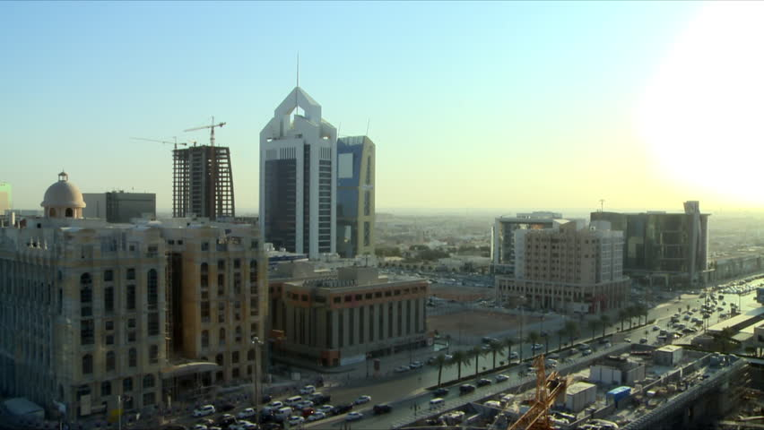 A pan of buildings in the capital city of Riyadh, Kingdom of Saudi Arabia showing the Al Faisaliyah Center and clear blue morning skies