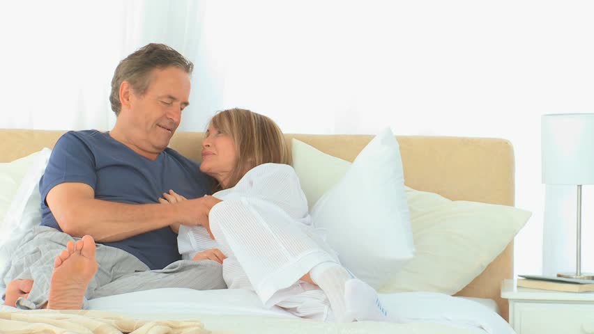 Couple at home sitting on floor looking at blueprint stock footage elderly couple talking on the bed hd stock footage clip malvernweather Choice Image