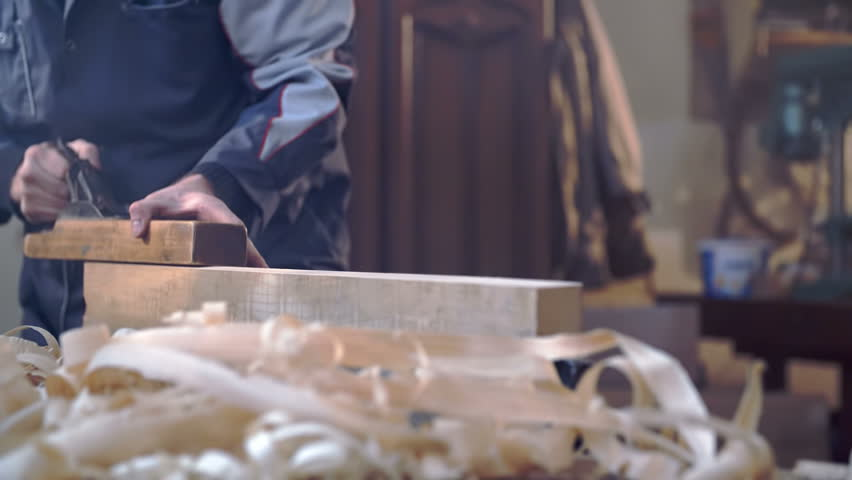 Man is smoothing out the piece of wood at homes working shop with vintage tools, footage is taken in slow motion.