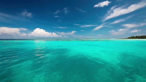 Clean turquoise lagoon on a tropical island with waves