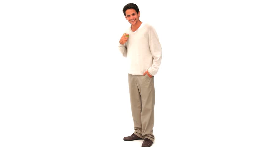 Relaxed man eating an apple against a white background