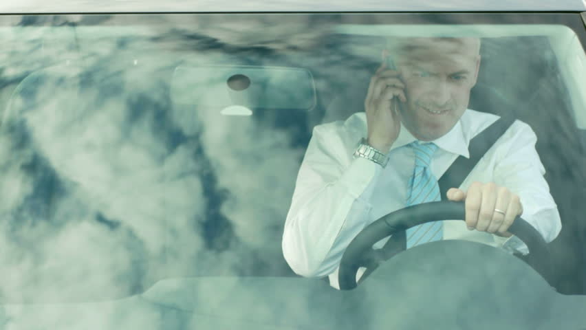 high angle view of caucasian mid adult business man on the phone while driving car