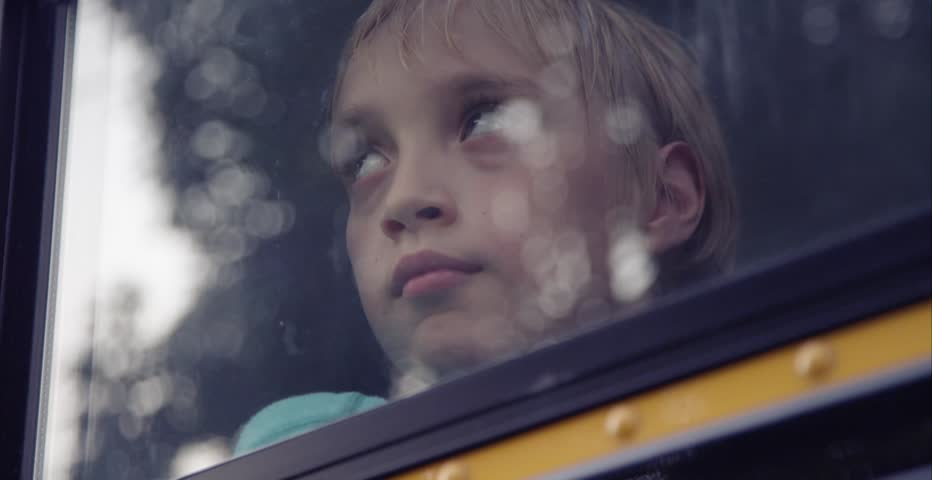 Sad child in school bus window