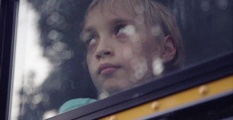 Sad child in school bus window