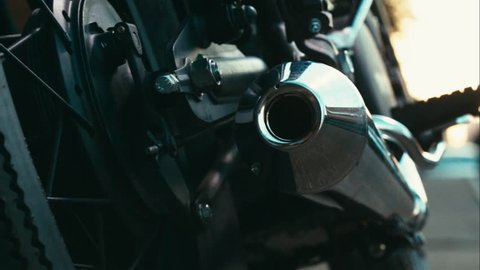 Close up left to right dolly sliding shot of a biker kickstarting the engine of a custom built cafe racer motorcycle