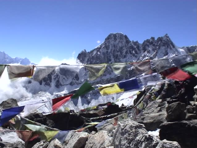 Buddhist prayer flags on Gokyo Ri in Nepal, with Mount Everest towering above in the distance.