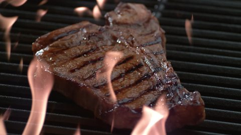 T-Bone steak on grill in slow motion, shot on Phantom Flex 4K
