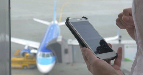 Close-up shot of female hands texting in messenger or typing sms on smart phone by the airport window. Boarding plane in background