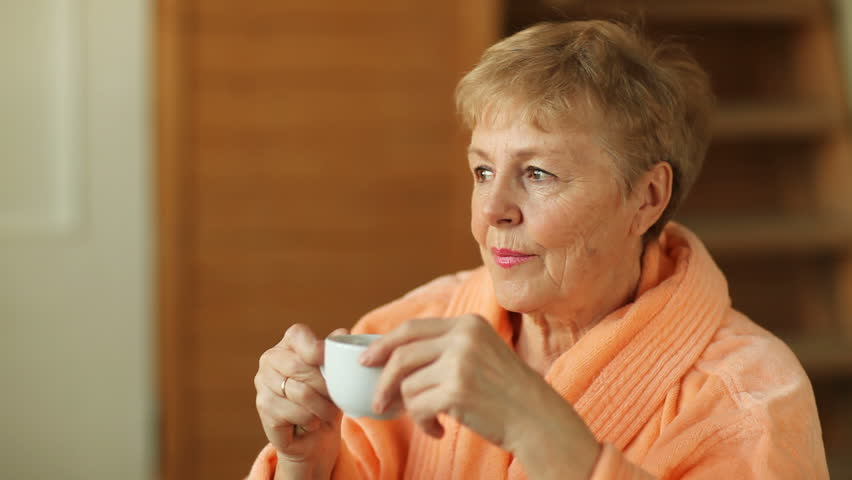 Thoughtful senior woman drinking coffee from white cup