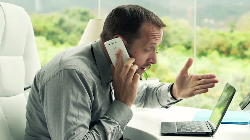 Angry businessman with laptop talking on cellphone by table in office