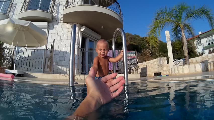 Child wants to jump into the swimming pool trying to get hold of parent's hand but scared