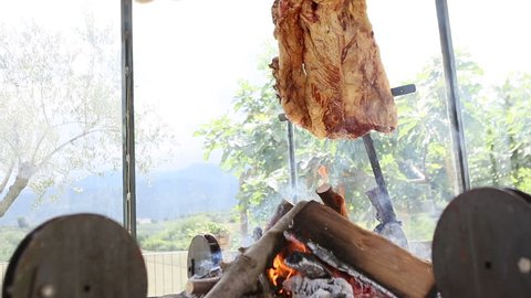 Montage of argentinian asado cooked on a spit on embers and slicing it up. Barbecued meat.