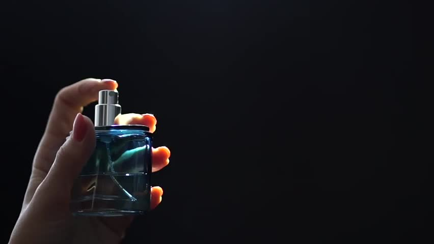 Slow motion video of perfume sprayed by beautiful girl hand