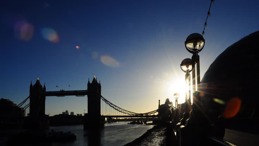 Early morning sunrise time-lapse behind the famous Tower Bridge over the River Thames in London, England. The sun moves behind lights on the embankment and then behind City Hall.