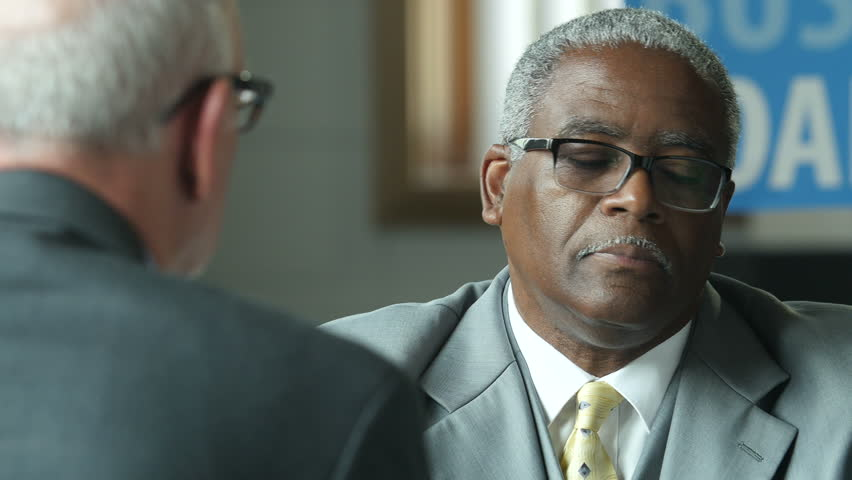 Black male banker meeting with senior male client to discuss a business loan