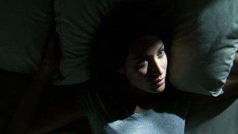 Woman lying awake in bed breathing heavily