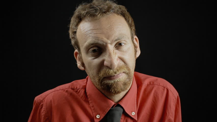 A man showing an envious expression. Medium close-up shot of the face on black background. Part of a series of depictions of feelings and emotions with professional actors.