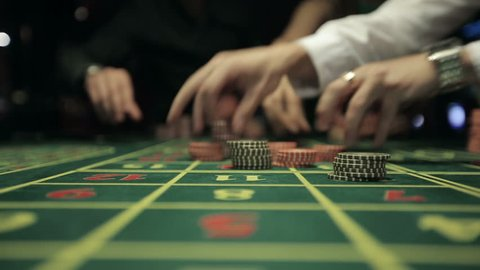 People placing bets for roulette in casino. Close up