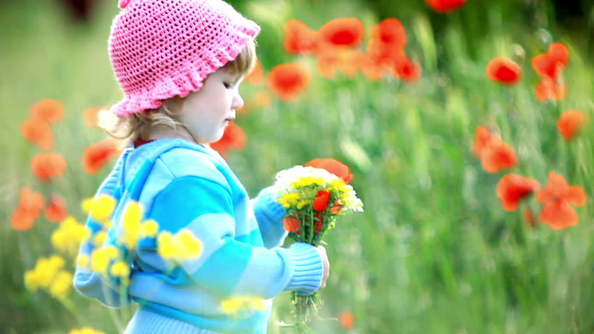 Beautiful child with flowers in her hands. She looks at camera