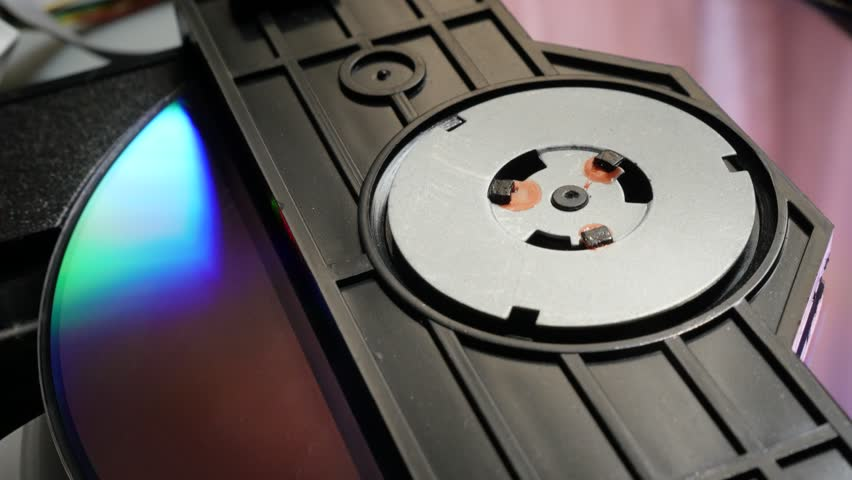 Rotating compact disk  in the reading mechanism close-up 4K 3840X2160 30fps UHD video - DVD or CD in player starting sequence 4K 2160p UltraHD footage
