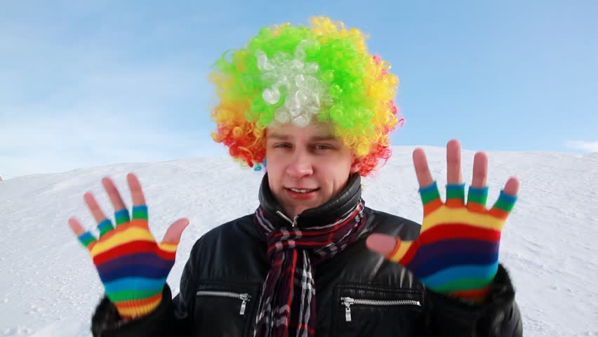 The man in colored wig does funny movement against the slope
