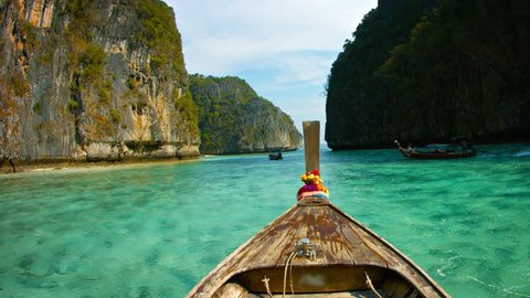 FullHD video - Crystal clear waters under Phi-Phi Island's seacliffs. from across the weathered wooden deck of a handmade longtail boat in Thailand